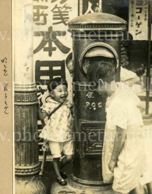 Japanese children playing near a postbox, circa 1930s.