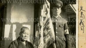 Japanese soldier and old person with flag, circa 1936.