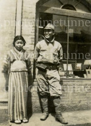 Japanese soldier and young woman outside a shop, circa 1940.
