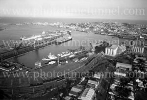 Aerial view of Newcastle Harbour, NSW, showing The Basin, grain silos and coal loading facilities, May 1974.