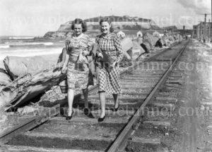 Women walking along the tramline on Nobbys breakwater, Newcastle, NSW, 1930s.